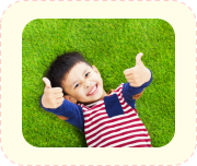 child lying on the grass doing OK sign